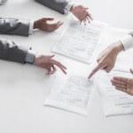 אנשי עסקים יושבים ליד שולחן ומעיינים במסמכים