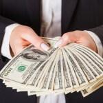 אשת עסקים מחזיקה שטרות כסף ביד