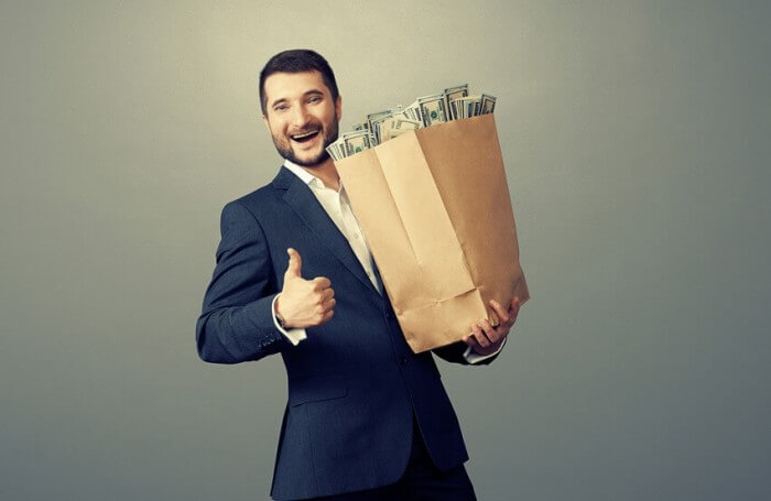 אדם מחזיק שקית נייר ובתוכה שטרות כסף