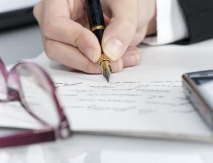 אדם חותם בעזרת עט על בקשת הלוואה
