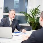 איש עסקים ועובד בנק מנהלים שיחה אודות הלוואה לעסק חדש