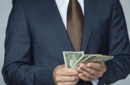 """אדם מחזיק שטרות כסף שהתקבלו מקרן קט""""י"""