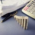 מטבעות כסף בערימה לצד עט ומסמכים